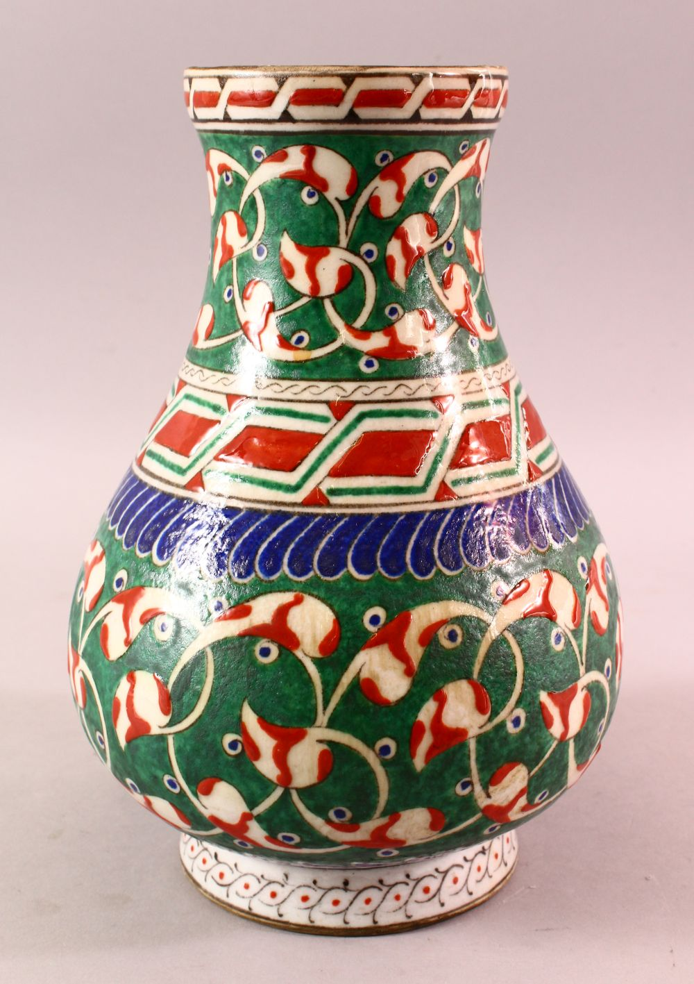 A TURKISH OTTOMAN 18TH CENTURY IZNIK VASE, with green and red motif decorations, 26cm