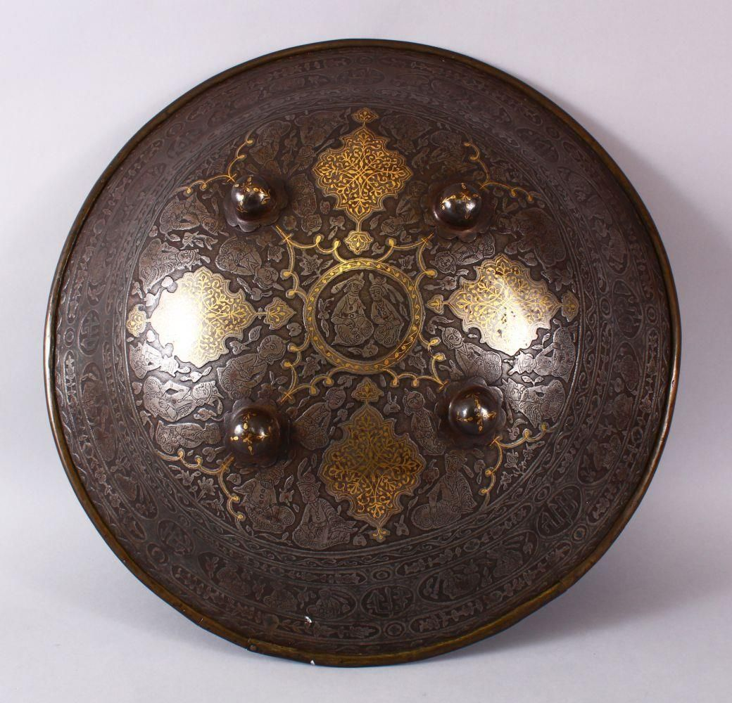 A LARGE 19TH CENTURY PERSIAN GILT DECORATED STEEL SHIELD, with carved decoration of figures, bands