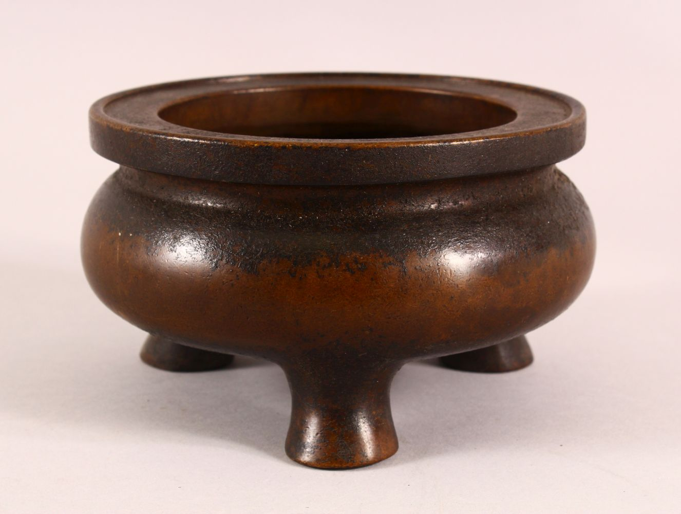 A CHINESE XUANDE STYLE BRONZE TRIPOD CENSER, underside with a mark, 16cm
