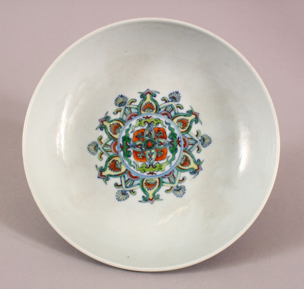 A CHINESE DOUCAI DISH decorated with lotus, yong zheng mark to base, 18cm diameter.
