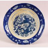 A CHINESE CRACKLE GLAZED PORCELAIN DISH, decorated with dragons and flora, 28cm diameter.