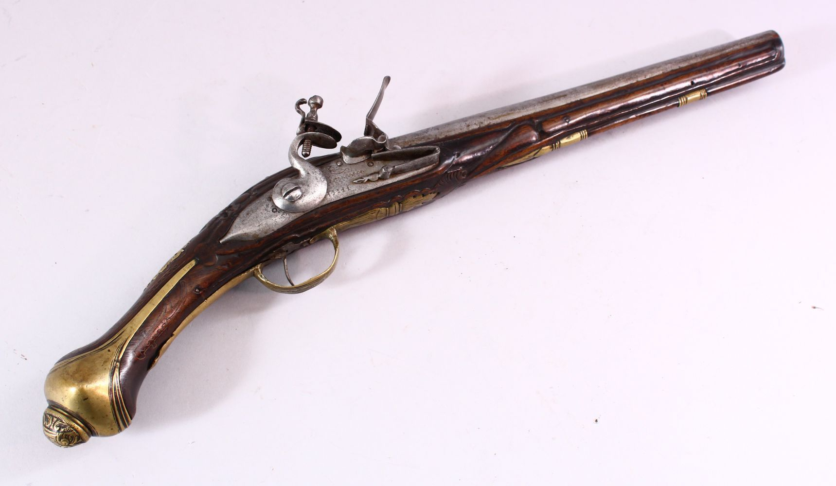 AN 18TH CENTURY ANGLO INDIAN FLINTLOCK PISTOL, engraved barrel, carved stock with wire inlaid