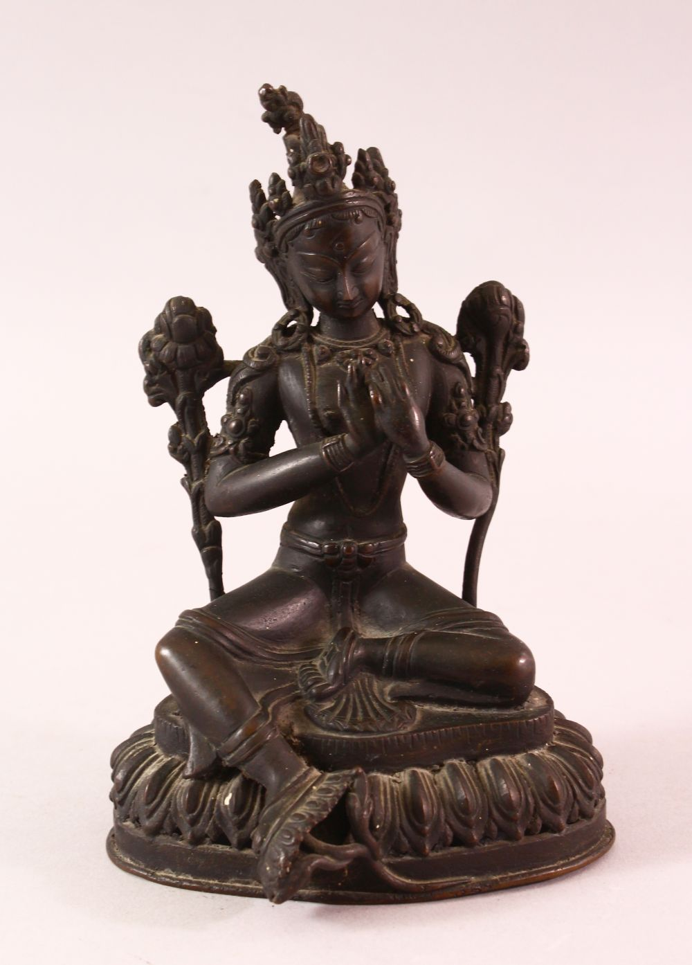 A 19TH CENTURY INDIAN BRONZE FIGURE OF SHIVA / DEITY, in a seated pose with hands together, upon