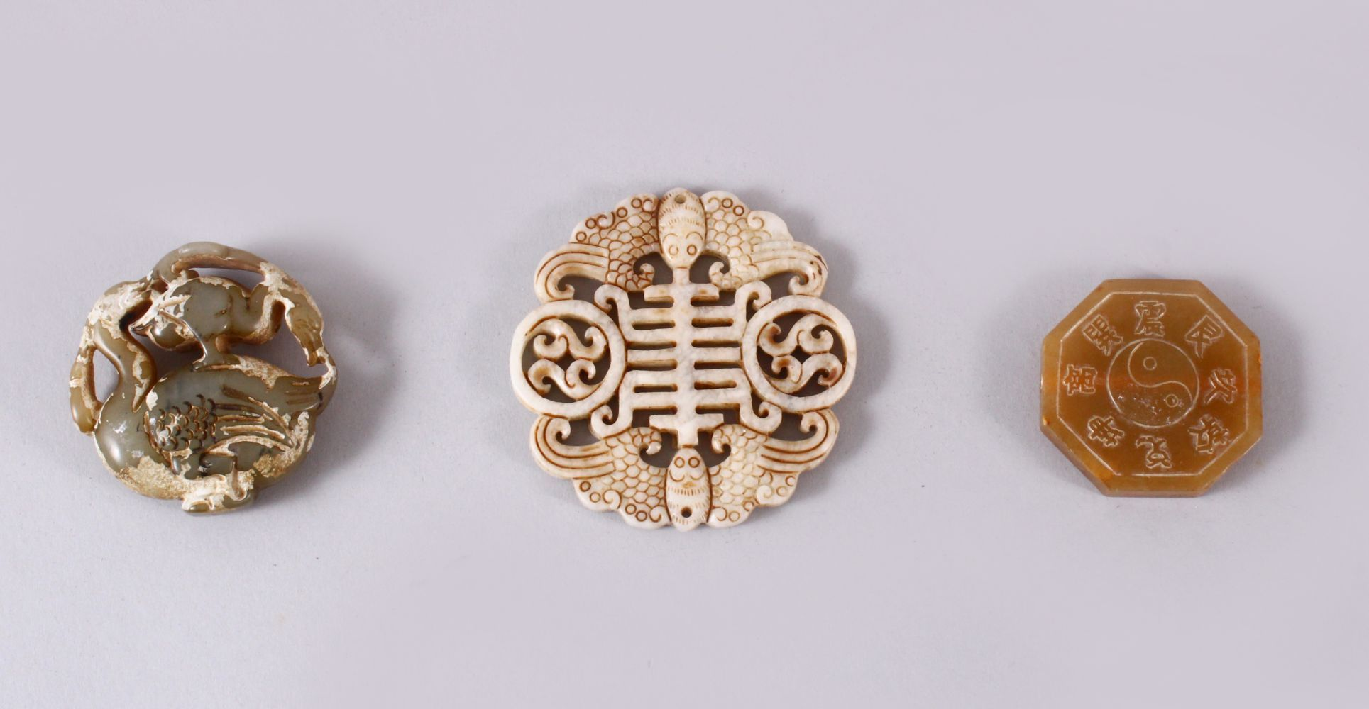 THREE CHINESE CARVED JADE PENDANTS, One carved in the form of TWIN BATS AND SYMBOLS, 6.5cm, one