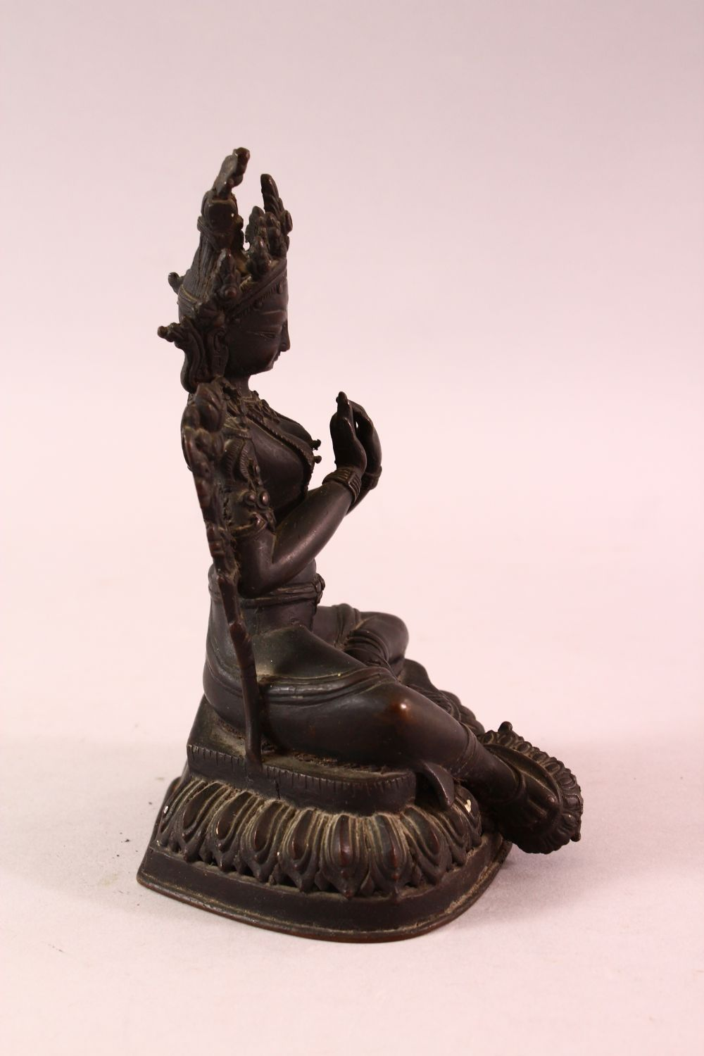 A 19TH CENTURY INDIAN BRONZE FIGURE OF SHIVA / DEITY, in a seated pose with hands together, upon - Image 2 of 5