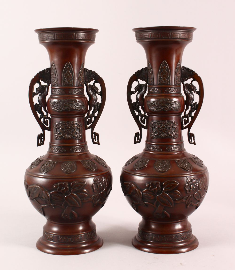 A PAIR OF JAPANESE RELIEF BRONZE VASES, with twin handles, relief birds and flora decoration, 40cm