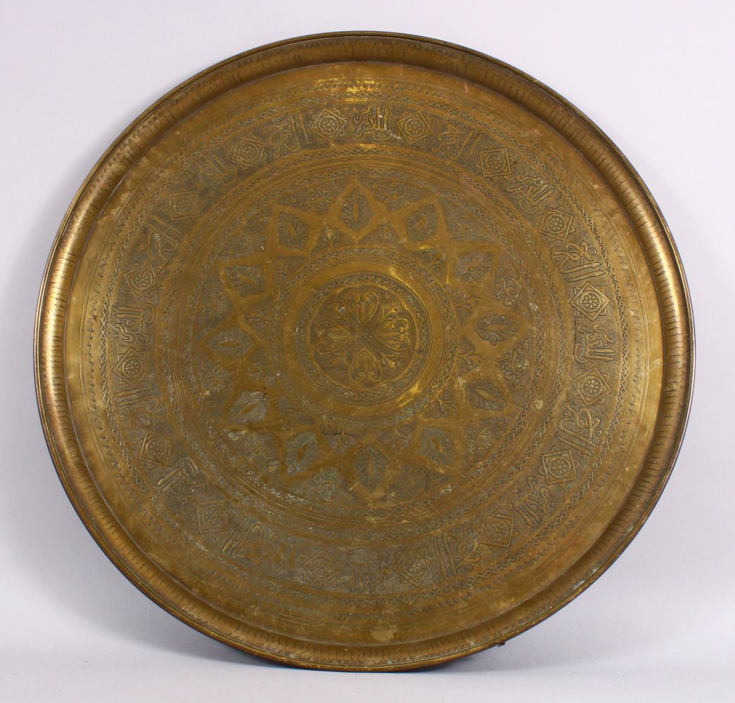 A LARGE 19TH CENTURY EGYPTIAN BRASS CHARGER / TRAY, with carved bands of calligraphy and motif