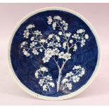 A 19TH CENTURY CHINESE BLUE & WHITE PRUNUS PORCELAIN DISH, the centre with a blue ground and