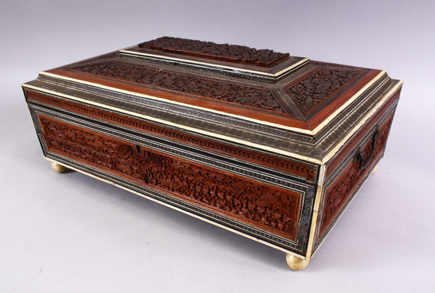 A 19TH CENTURY ANGLO INDIAN INLAID LIDDED SEWING BOX, with carved wood depicting figures and animals