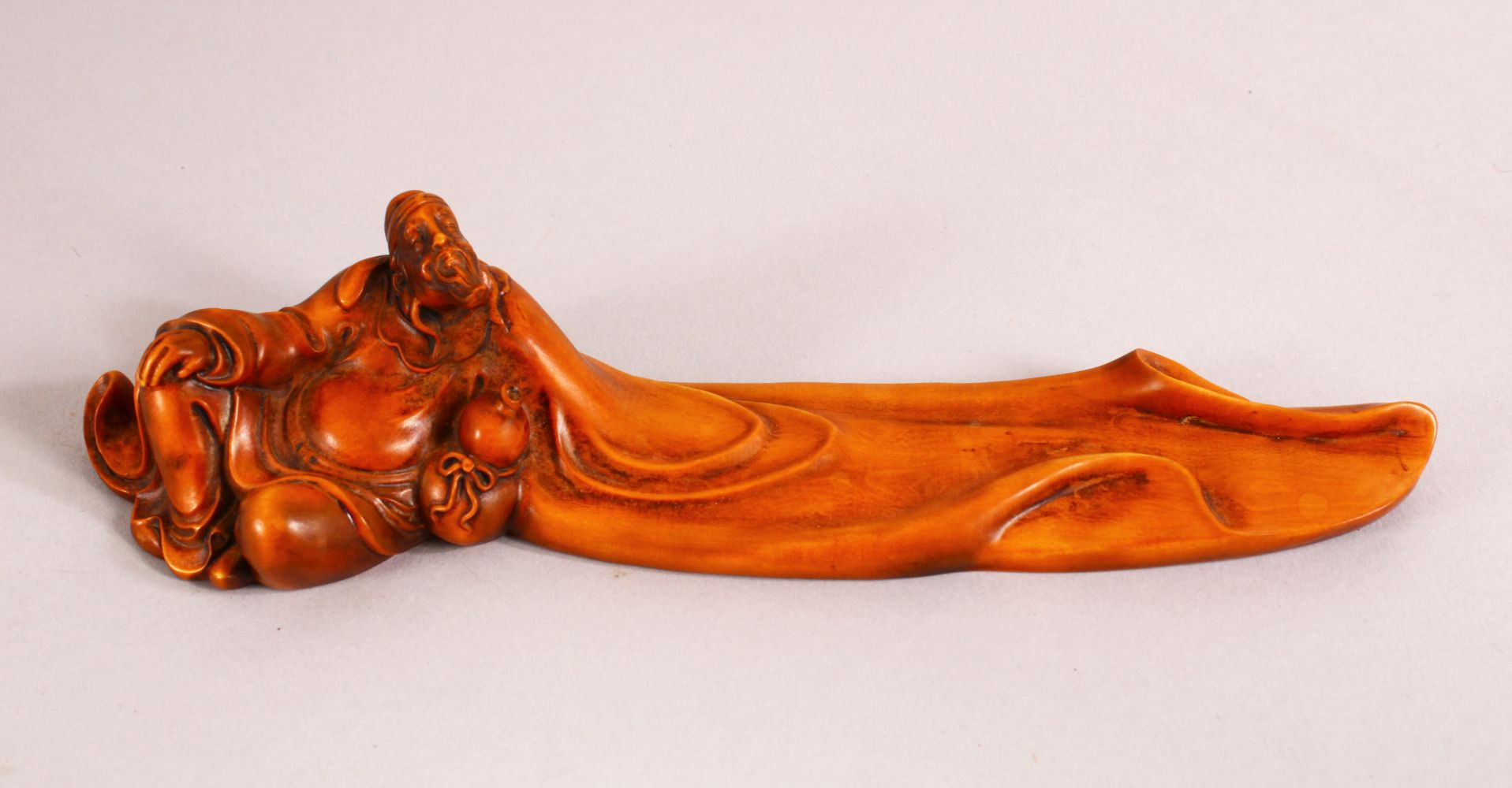 50A CHINESE CARVED WOOD FIGURE OF ROHAN OR IMMORTAL, seated with a drinking vessel, 20cm