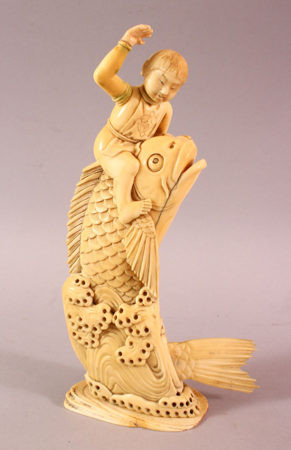 A JAPANESE MEIJI PERIOD CARVED IVORY FISH OKIMONO, the fish emerging from the water with a boy on