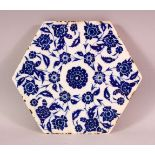 A FINE TURKISH BLUE AND WHITE HEXAGONAL POTTERY TILE, painted with stylised flowers, 24cm diameter.