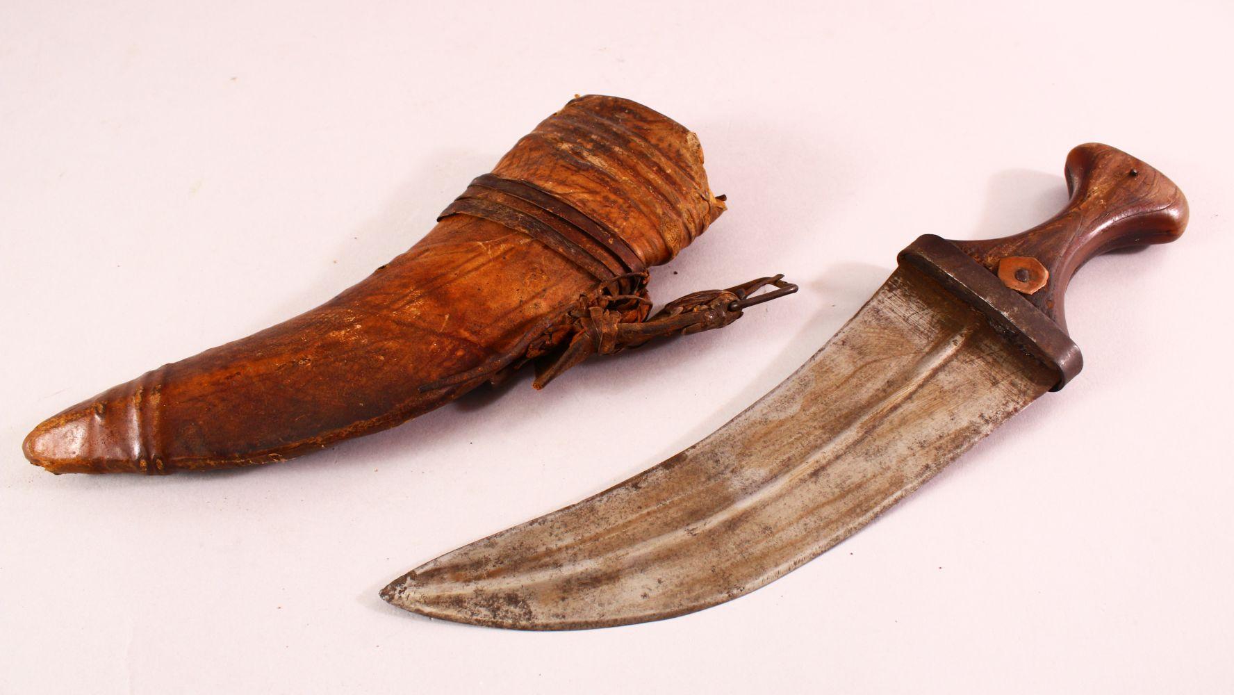 AN ARAB JAMBIYA DAGGER, with horn handle and hide scabbard, 31cm long.