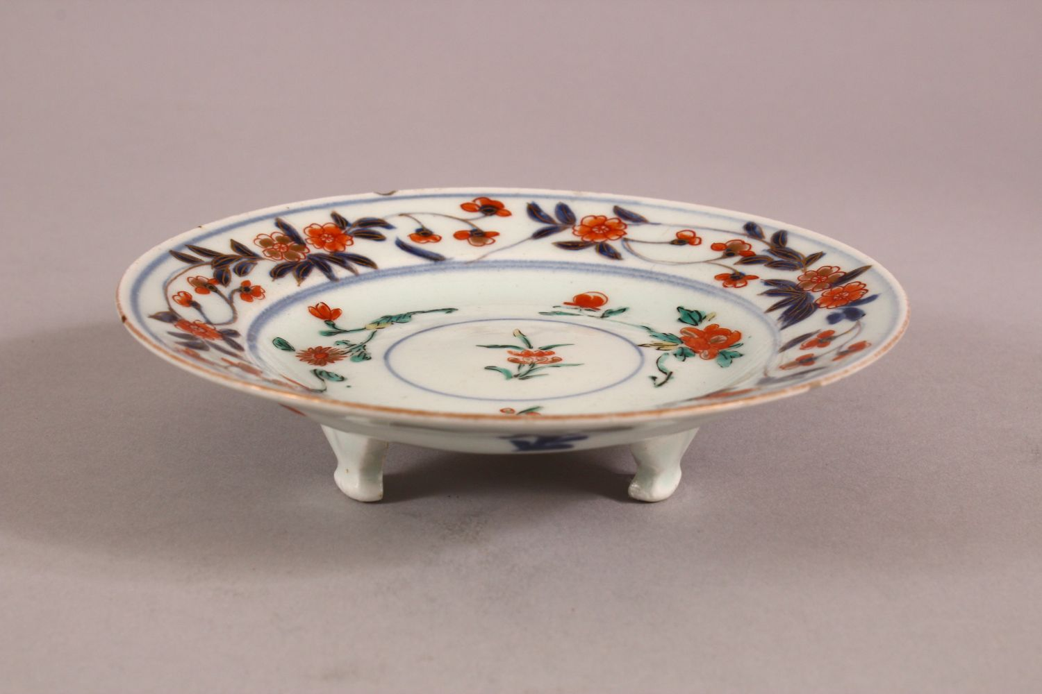 A SMALL JAPANESE IMARI CIRCULAR STAND, painted with a band of flowers on three scrolling feet, 13. - Image 2 of 3