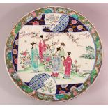 A LARGE JAPANESE POLYCHROME PORCELAIN CHARGER, depicting females in a garden setting, the