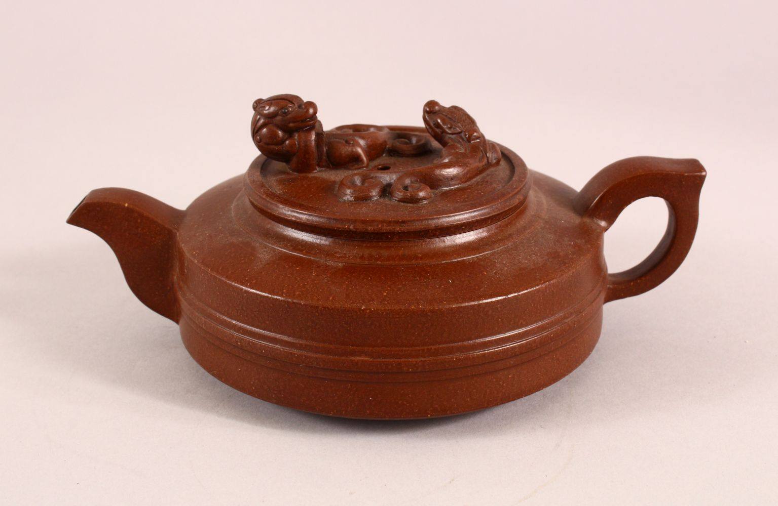 A CHINESE YIXING CLAY TEAPOT, with moulded beast like figures, the underside of the pot and lid with