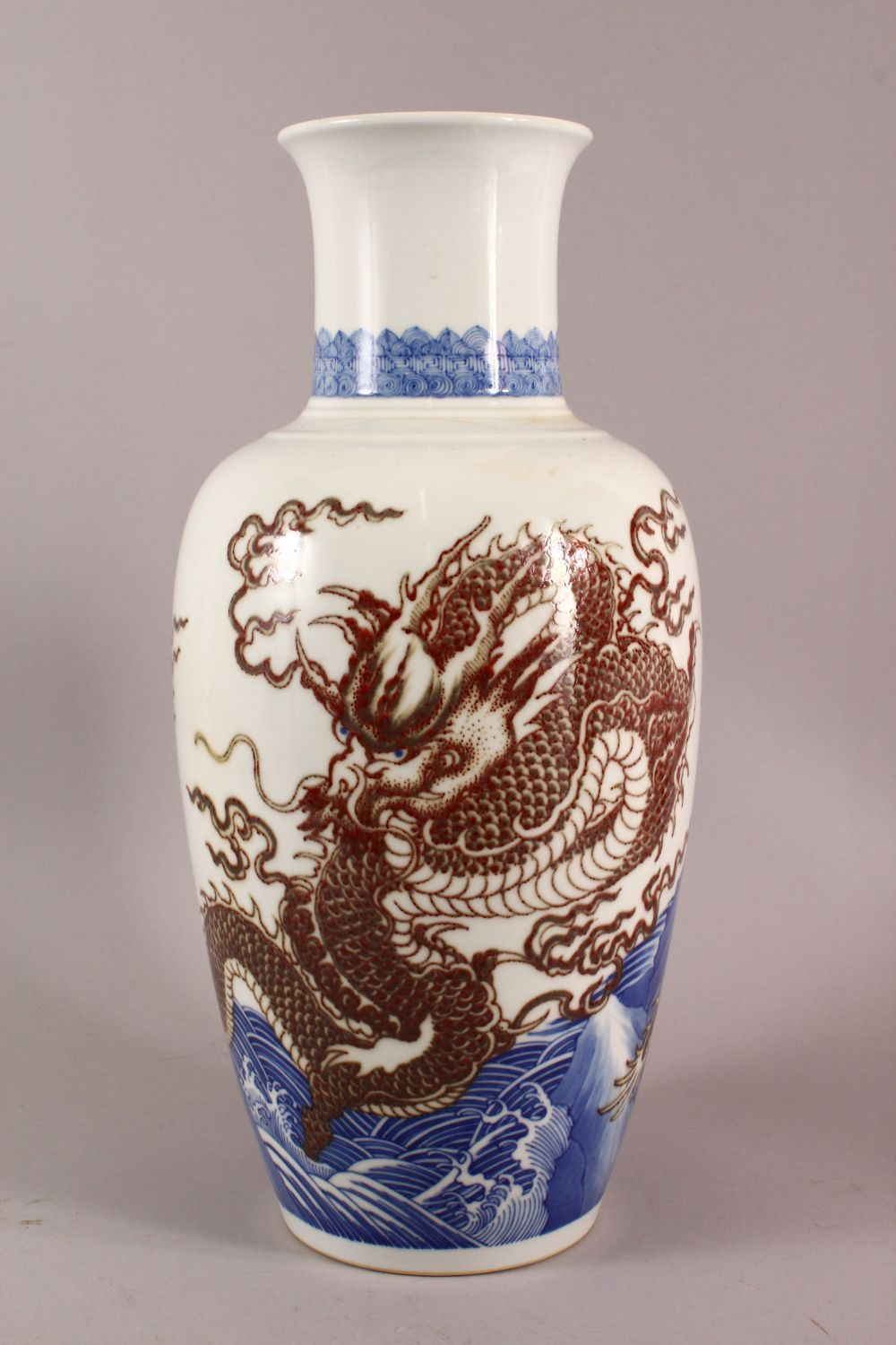 A LARGE CHINESE UNDERGLAZE BLUE & COPPER RED PORCELAIN VASE, decorated with dragons amongst waves,