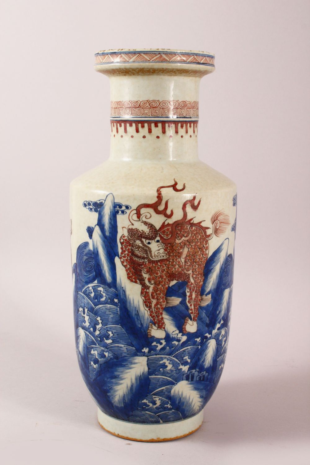 A CHINESE UNDERGLAZE BLUE & COPPER RED PORCELAIN VASE, decorated with lion dogs and waves, six
