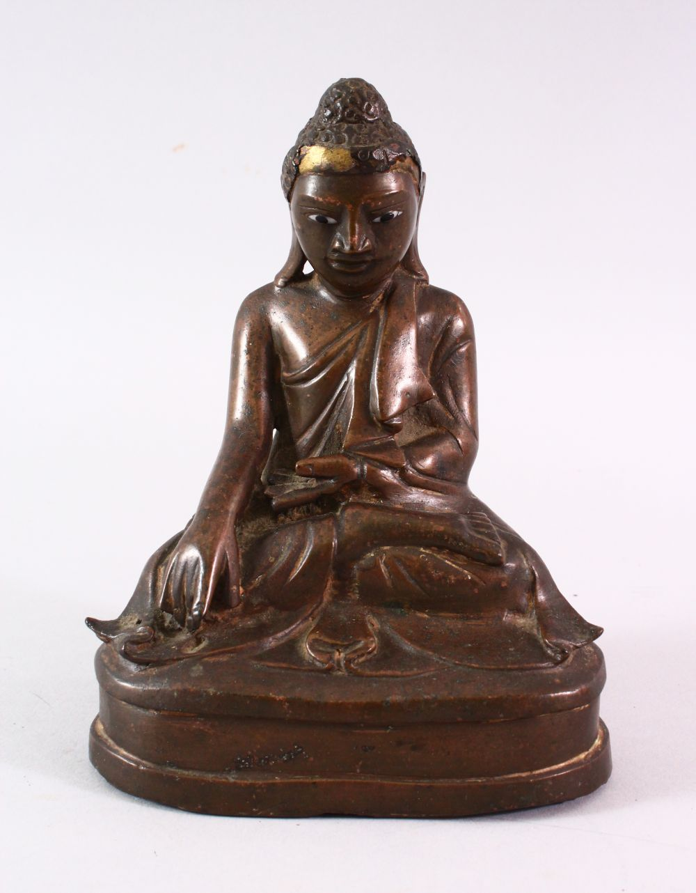 A BRONZE BUDDHA with glass inset eyes, 16cm high.