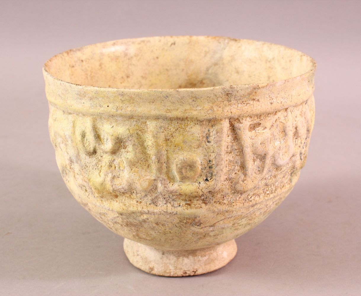 A 12TH CENTURY KUFIC SCRIPT GLAZED POTTERY BOWL, the exterior with moulded script, 15cm diameter,
