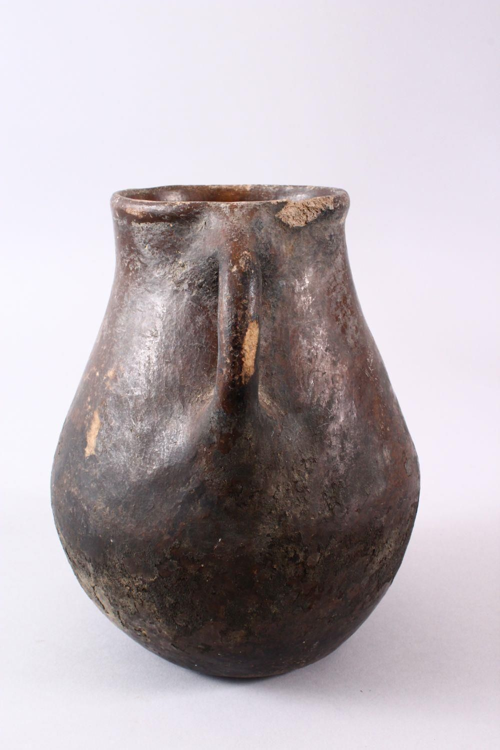 A 10TH CENTURY IRANIAN POTTERY TWIN HANDLE JUG, 22cm high. - Image 2 of 5