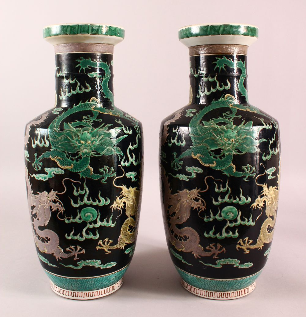 A LARGE PAIR OF CHINESE FAMILLE NOIR PORCELAIN DRAGON VASES, each vase with a black ground depicting