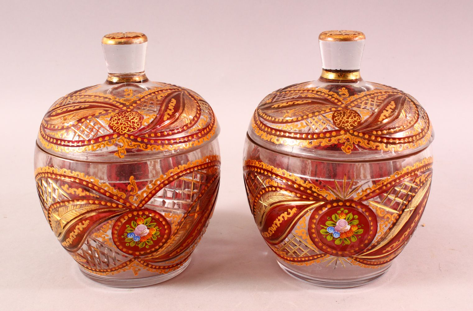 A PAIR OF BOHEMIAN RED ENAMELLED GLASS JARS, each with enamel and gilt work, 20cm each