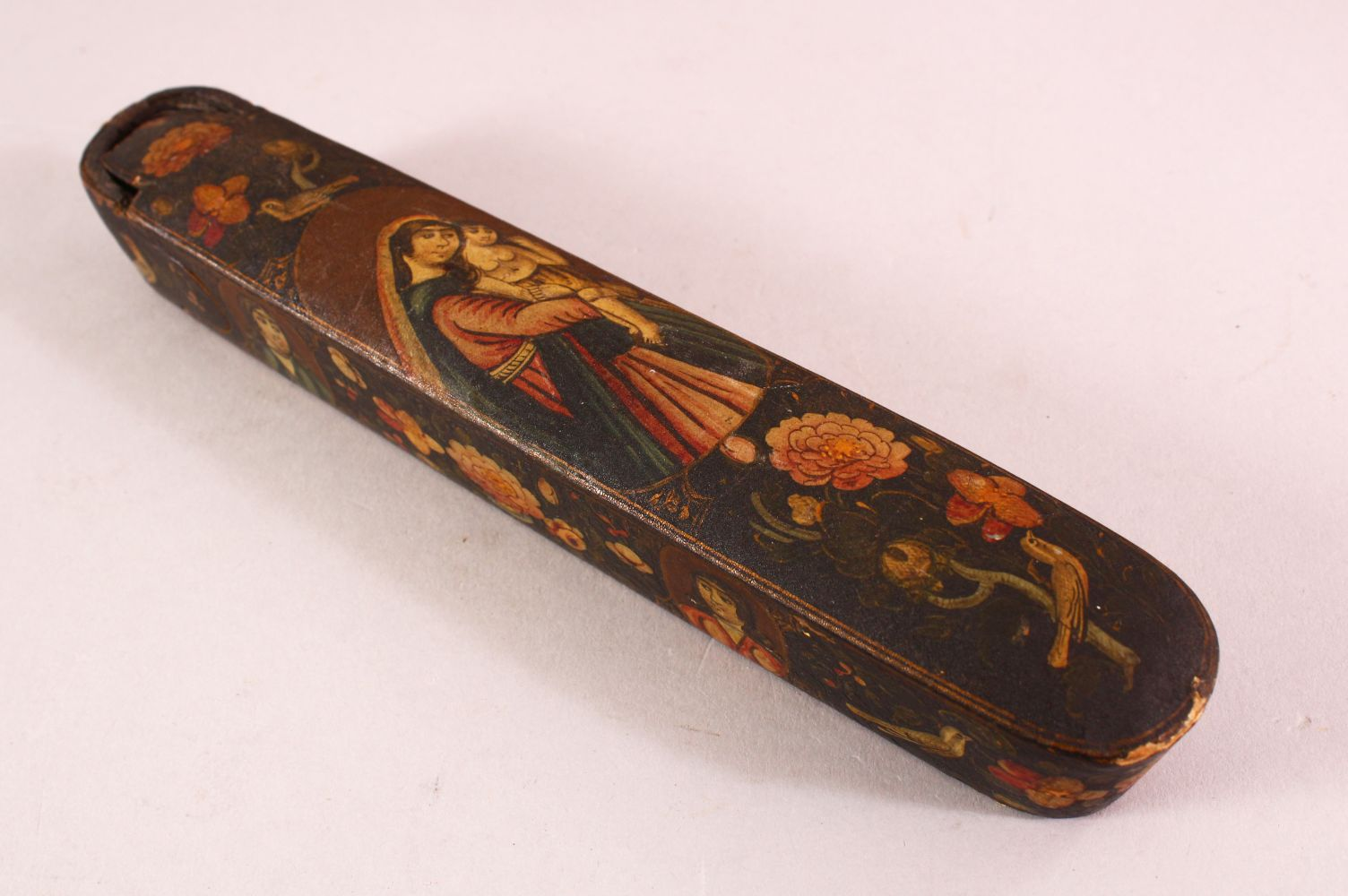 A PERSIAN QAJAR LACQUERED PEN BOX containing the brass inkwell, 23cm long.