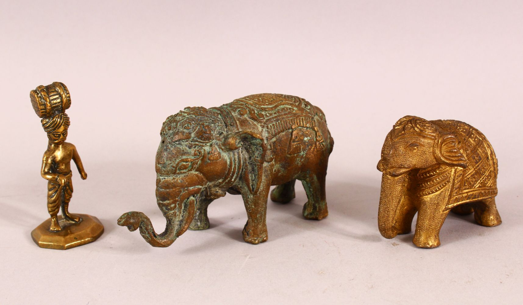 THREE INDIAN GILT METAL FIGURES, two elephant and a figure.