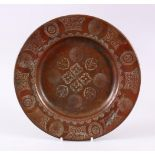 A 19TH CENTURY ISLAMIC CALLIGRAPHIC COPPER DISH, with floral motif and panels of calligraphy, 24cm