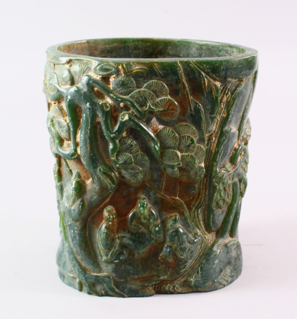 A CHINESE GREEN HARDSTONE BRUSH POT, carved with figures and trees, calligraphy, 15.5cm high.