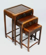 A GOOD NEST OF THREE CHINESE HARDWOOD TABLES, each with carved frieze, largest 60cm high, 43cm wide,