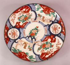 A LARGE JAPANESE MEIJI PERIOD PORCELAIN IMARI CHARGER, depicting shi shi dogs with floral