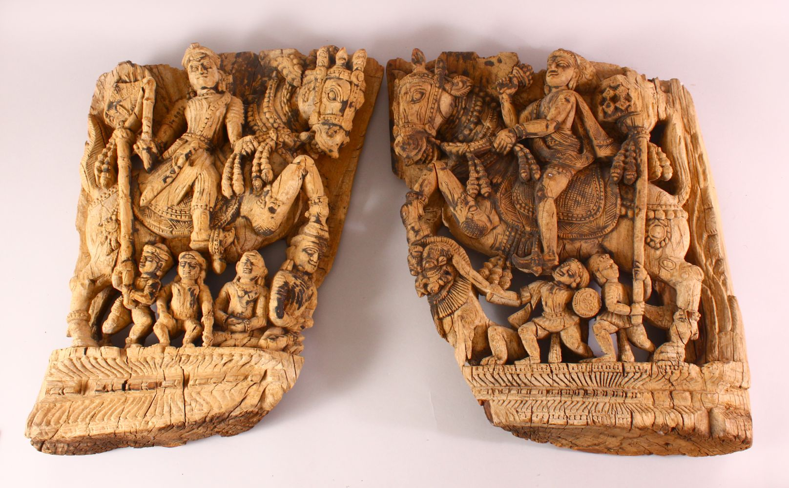TWO 18TH/19TH CENTURY SOUTH INDIAN CARVED WOODEN PANELS, each depicting a figure on horseback with