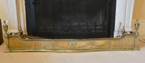 AN ADAM DESIGN BRASS FENDER and five irons. 4ft 8ins long.