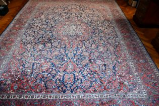 A VERY GOOD LARGE PERSIAN FLORAL CARPET, mainly in red and blue. 11ft 6ins x 8ft 6ins.