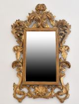 A SMALL ITALIAN FLORENTINE GILTWOOD MIRROR with scrolls. 1ft 11ins x 1ft 1ins.