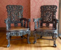 A GOOD PAIR OF CHINESE CARVED AND PIERCED ARMCHAIRS with solid seats, dragon arms and foliage.