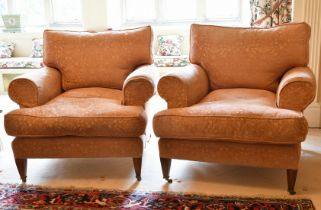 A GOOD PAIR OF LARGE DEEP EASY ARMCHAIRS on tapering legs with brass castors.