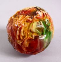 A CHINESE CARVED BAKELITE OR CHERRY AMBER ZODIAC BALL, carved with animals, 9cm diameter.