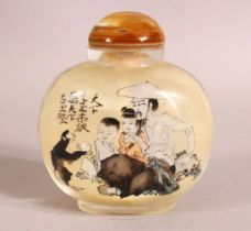 A CHINESE REVERSE PAINTED SNUFF BOTTLE - decorated with figures and moneys in landscapes - with