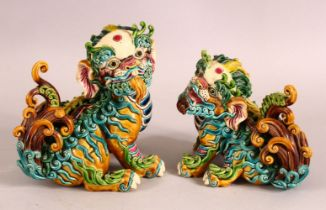A PAIR OF 20TH CENTURY CHINESE SANCAI POTTERY LION DOGS - the mirrored pair both looking on - one