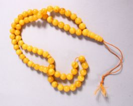 A CHINESE QING DYNASTY CARVED AMBER PRAYER BEADS / ROSARY NECKLACE, comprising 66 beads, 3 spacers
