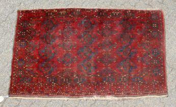 A SMALL PERSIAN BASHIR RUG, red ground with three small rows of four motifs. 5ft x 3ft.