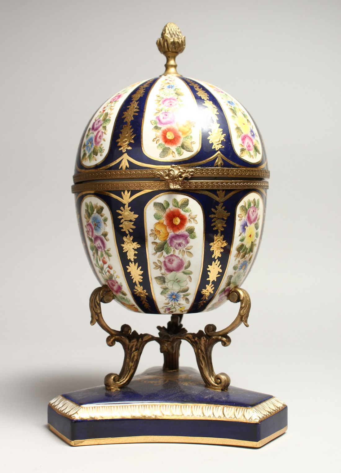 A LARGE SEVRE STYLE BLUE AND GILT EGG SHAPED CASKET AND COVER, painted with flowers on a