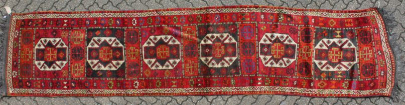 A LONG PERSIAN RUNNER with six main medallions 14ft long x 3ft 3ins wide.
