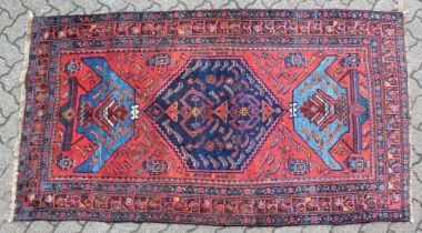 A GOOD SMALL PERSIAN RUG, deep red ground with a central large medallion, flanked by stylised vases.