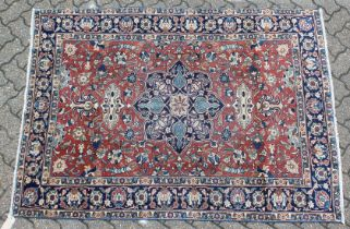 AN EARLY 20TH CENTURY PERSIAN RUG, claret ground with stylised decoration, within a blue ground