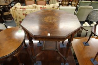 AN EDWARDIAN INLAID ROSEWOOOD OCTAGONAL TOP CENTRE TABLE with tapering legs and porcelain castors.