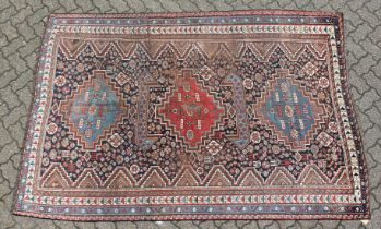 A SHIRAZ RUG, with three large central medallions, in a narrow border. 8ft 7ins x 5ft 9ins.